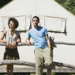 Stock Photo: Couple leaning on wooden fence next to tent