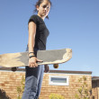 Teenage girl holding skateboard — Stock Photo