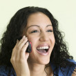 Young woman laughing on cell phone — Stock Photo