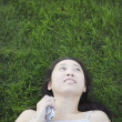 Woman laying on grass with cell phone — Stock Photo
