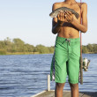 Young boy holding a freshly-caught fish - Stock Photo