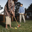 Couple playing croquet in yard — Stock Photo