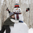 Boy hugging snowman — Stock Photo #18572051