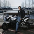 Young man on motorcycle at marina — Stock Photo