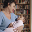 Middle-aged woman cradling her baby granddaughter — Stock Photo #18572167
