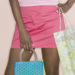 Midsection of woman holding shopping bags - Stock Photo