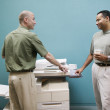 Two businessmen talking at copy machine — Stock Photo