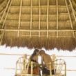 Couple kissing underneath thatch roof — Stockfoto