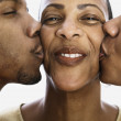 Close up of son and daughter kissing mother — Stock Photo