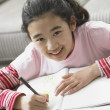 Portrait of young girl doing homework — ストック写真