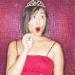 Asian woman wearing evening dress and tiara and eating lollipop — Stock Photo