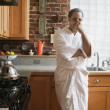 Portrait of man in bathrobe in kitchen — Stock Photo