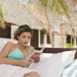Young woman reading on a couch outdoors — Stock Photo