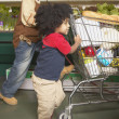 Young African American brothers pushing shopping cart — Stock Photo #18573375