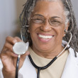 Portrait of female doctor holding stethoscope up — Stock Photo