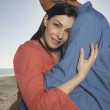 Portrait of couple hugging at beach - Stock Photo