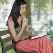 Young woman eating an apple and reading outdoors — Stock Photo