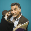 Portrait of man with briefcase and files talking on cell phone - Stock Photo