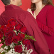 Hispanic man surprising Hispanic woman with roses — Stock Photo