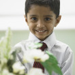 Portrait of young boy holding flowers — Stock Photo #18573921