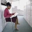 Businesswoman reading files in office — Stok fotoğraf