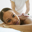 Portrait of woman receiving back massage - Stock Photo