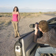 Man in car taking woman's picture — Stockfoto