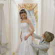 Stock Photo: Young bride-to-be trying on her gown with the help of an employee