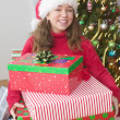 Royalty-Free Stock Photo: Portrait of girl in Santa hat in front of Christmas tree holding gifts