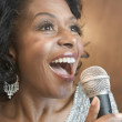 Stock Photo: Close up of AfricAmericwomsinging with microphone