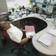 Businessman sleeping at desk in office — Stock Photo