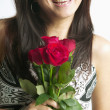Woman holding roses and smiling - Stock Photo