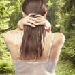Rear view of woman standing in forest running hands through hair - Stock Photo