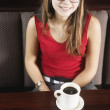 Woman in booth with cup of coffee — Stock Photo