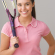 Portrait of teenage girl smiling and holding tennis racket — Stock Photo