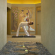 Woman doing yoga in spa room - Stock Photo