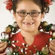 Young girl holding a wreath of jingle bells around her neck — Stock Photo #18575429