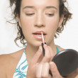 Young woman applying lip gloss — Stock Photo
