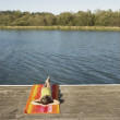 Stock Photo: Young girl relaxing by a lake