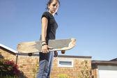 十几岁的女孩举行滑板 — 图库照片