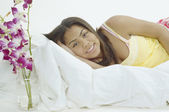 Adolescente sorrindo para a câmera na cama — Foto Stock