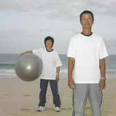 Couple standing with ball at beach — Stock Photo