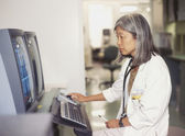 Mature female doctor working on computer — Stock Photo