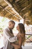 Joven pareja abrazándose en una choza de paja — Foto de Stock