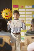 Jeune garçon en salle de classe brandissant classés feuille de math — Photo