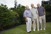 Portrait of three elderly men standing in yard — Stock Photo