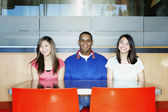 Portrait of three teenagers sitting at table — Stock Photo