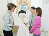 Tailor helping young women pick bridal fabric — Stock Photo