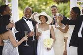 Bruiloft gasten roosteren bruid en bruidegom — Stockfoto