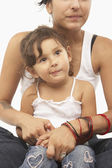 Mamma håller sin dotter i hennes knä — Stockfoto